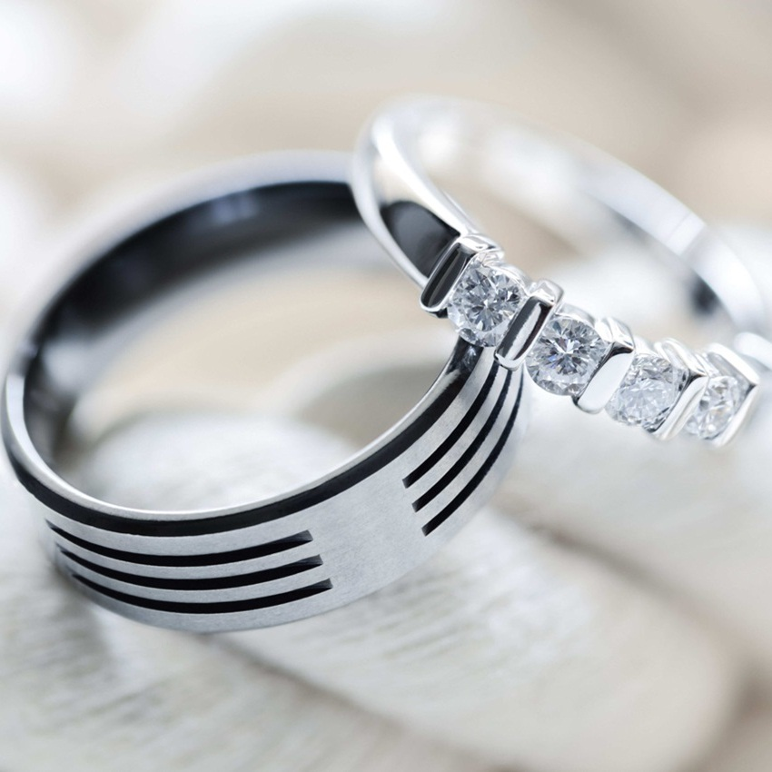Two silver platinum and titanium diamond wedding rings on white rope background