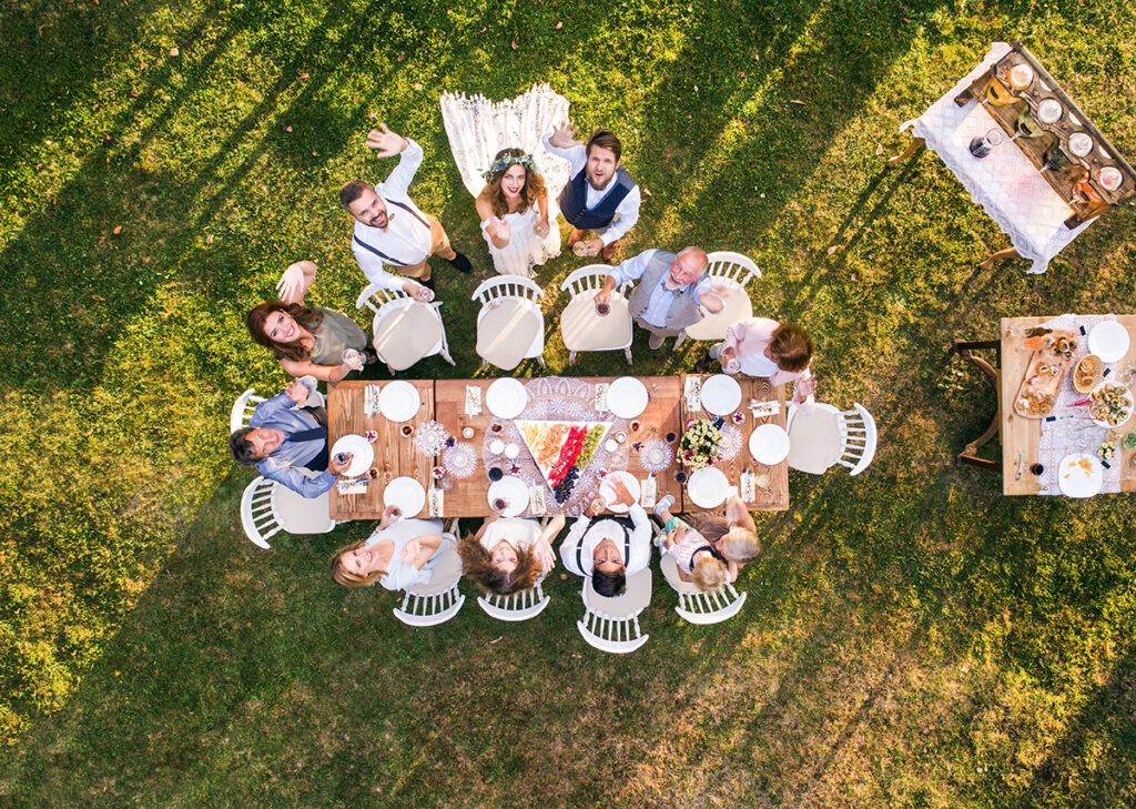 aerial shot via drone capturing bride and groom, family at wedding table waving to camera